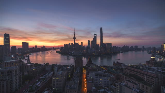 4K Time lapse of urban skyline and cityscape at sunrise in Shanghai China.(Night to Day)