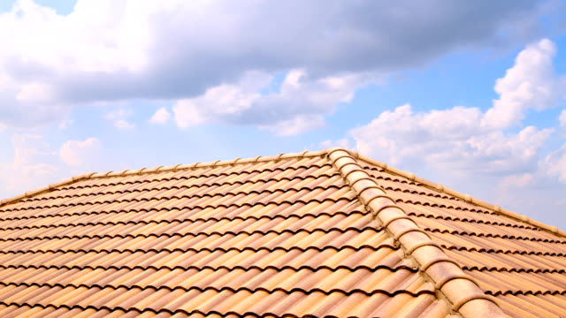 time lapse of white quick clouds passing over a roof made of light brown tiles. hd - piastrella video stock e b–roll