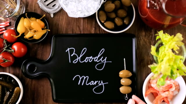 Time lapse. Olives, pickles, celery, and cocktail shrimp to garnish bloody mary cocktail. video