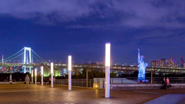 4k time lapse panorering skott: rainbow bridge viewpoint och replika staty av liberty at night - odaiba kaihin koen bildbanksvideor och videomaterial från bakom kulisserna