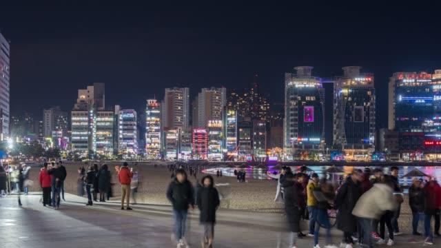 stockvideo's en b-roll-footage met 4k time-lapse: voetgangers toeristische wandelen op gwangalli strand in de stad busan, zuid-korea - shop sign