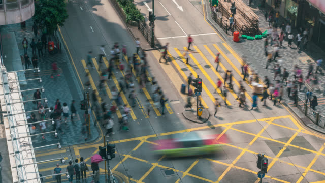 time lapse people and taxi cabs crossing a very busy crossroads in tsim sha tsui district hong kong in china - центральный район стоковые видео и кадры b-roll