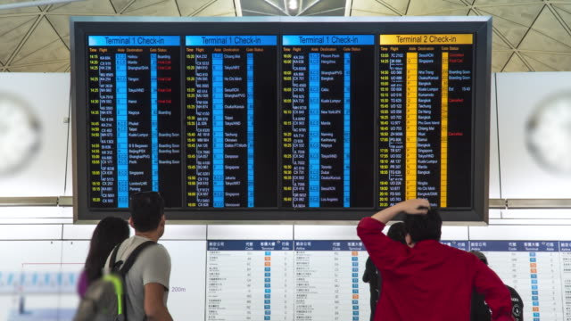 Time lapse. People in international airport looking at the flight information board, checking their flights.