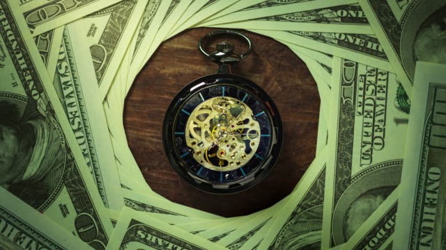 Time lapse pocket watch on the floor among dollar banknote stacking in darkness.