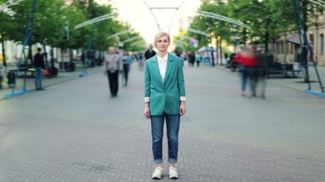 time lapse portrait of attractive blonde standing outdoors in the street alone - tożsamość pojęcia filmów i materiałów b-roll