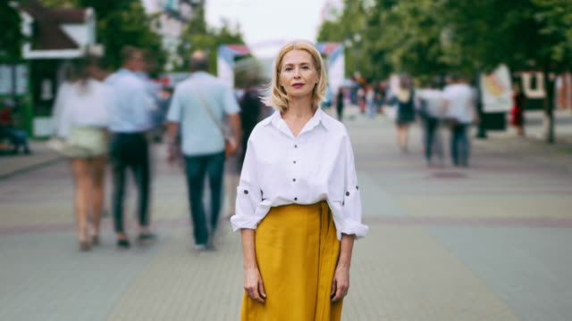 Time lapse portrait of beautiful mature lady with serious face in city street Time lapse portrait of beautiful mature lady with serious face in city street standing alone looking at camera. Summer town, people and modern life concept. individuality stock videos & royalty-free footage