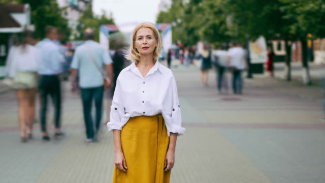 Time lapse portrait of good-looking mature woman in elegant clothing in street Time lapse portrait of good-looking mature woman in elegant clothing in street standing alone looking at camera with serious face. People, life and summer concept. stationary stock videos & royalty-free footage