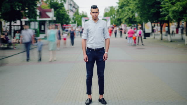 Time lapse portrait of handsome Arabian man in casual clothing outdoors in city Time lapse portrait of handsome Arabian man in casual clothing outdoors in city street standing alone with serious face looking at camera while people moving around. standing stock videos & royalty-free footage