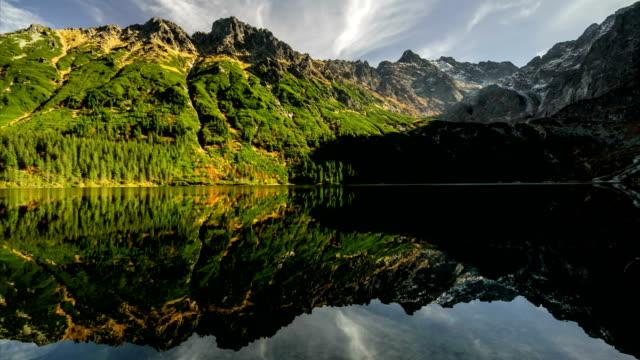 zaman atlamalı yansımasıdır bulutlar ve göl morskie oko, tatras dağlar, polonya manzara arka plan gölge canavarlar - zakopane stok videoları ve detay görüntü çekimi