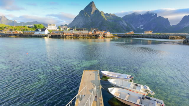 Time lapse shot of  Norwegian fishing village  at the Lofoten Islands in Norway. Dramatic sunset clouds moving over steep mountain peaks. video