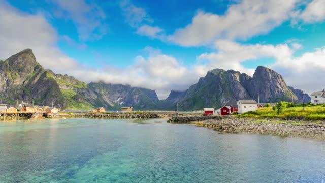 vídeos de stock e filmes b-roll de time lapse shot of  norwegian fishing village  at the lofoten islands in norway. dramatic sunset clouds moving over steep mountain peaks. - lofoten