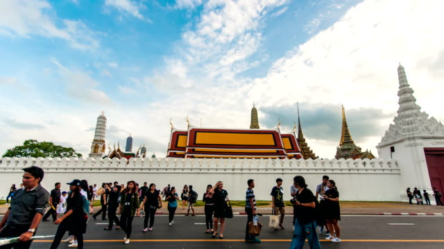 Time Lapse shot of Numerous People walking on Road with Thai Temple Background, Bangkok, Thailand. Panning shot. video