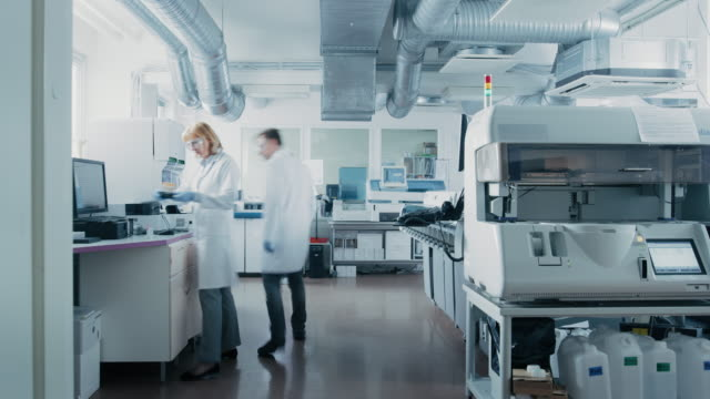 Time Lapse Shot of Team of Research Scientists Working On Computer, with Medical Equipment, Analyzing Blood and Genetic Material Samples with Special Machines in the Modern Laboratory.