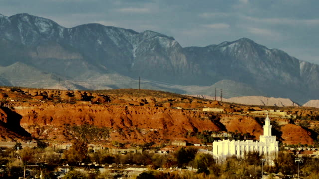 time lapse shot of the city of st george in southern utah as the sun goes down with the white mormon temple that stands out from the red desert landscape - salt lake stan utah filmów i materiałów b-roll