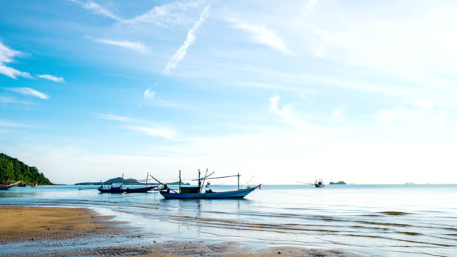 Time lapse shot of Traditional Fishing Boat on Beach with Blue Sky and Wave video