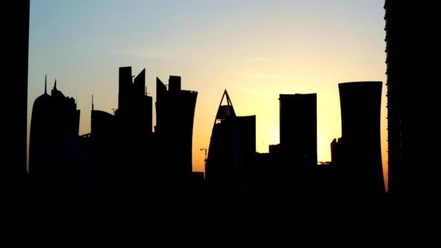 vidéos et rushes de temps qui passe à la silhouette moderne de la ville du coucher du soleil - doha