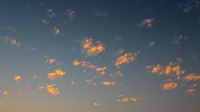 青い空の夕日に移動する小さな雲のタイムラプス ビデオ