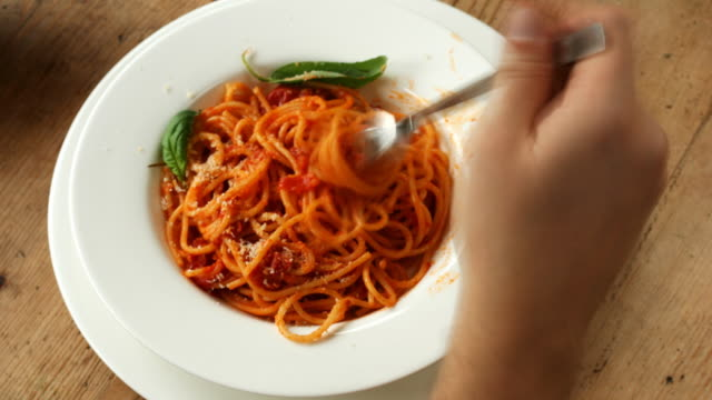 Time Lapse: Spaghetti with tomato sauce eaten in 15 seconds A macro shot of a tasty spaghetti dish with tomato sauce and  parmesan cheese. spaghetti stock videos & royalty-free footage