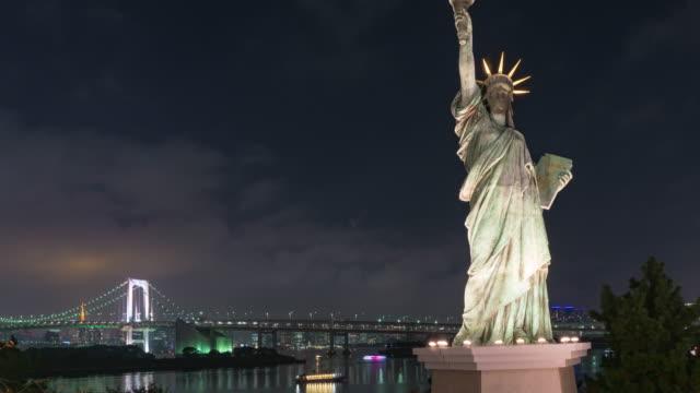 4k tidsfördröjning: frihetsgudinnan i odaiba med rainbow bridge på natten. - odaiba kaihin koen bildbanksvideor och videomaterial från bakom kulisserna