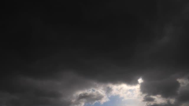 zeitraffer: stürmische wolken bedecken die sonne und beschneit es kurz. 4k - gewitter stock-videos und b-roll-filmmaterial
