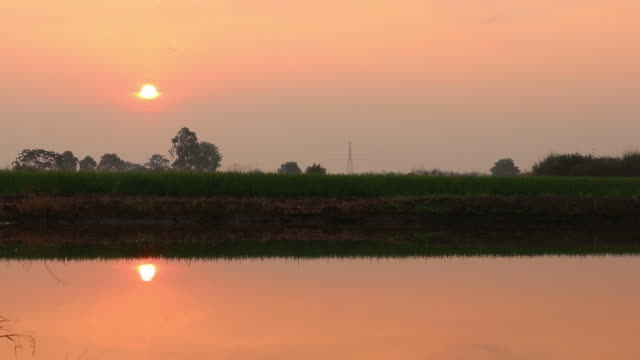 Time lapse; Sun rose reflecting water.
