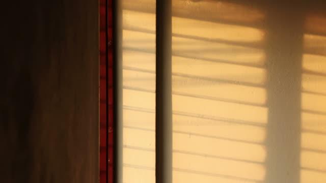 時間流逝: 陽光透過窗戶百葉窗的陰影。 - 影 個影片檔及 b 捲影像