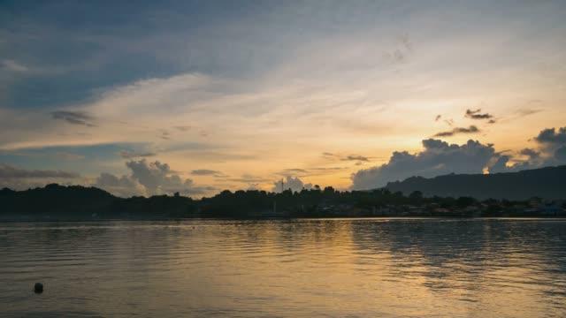 vídeos de stock e filmes b-roll de time lapse sunrise colorful sky over bandaneira village indonesia - arquipélago