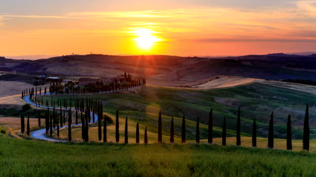 Time lapse Sunset over the rolling hills and winding road in Tuscany, Italy