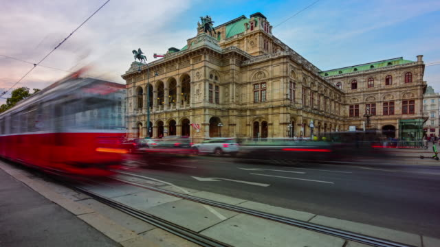 vídeos de stock, filmes e b-roll de cena do por do sol do lapso de tempo da estrada do tráfego e dos povos que andam na frente da casa de ópera viennese, viena, áustria - áustria