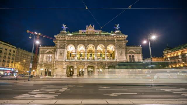 ウィーン・オペラハウスの前を歩く交通道路と人々のタイムラプスサンセットシーン、ウィーン、オーストリア - オペラ点の映像素材/bロール