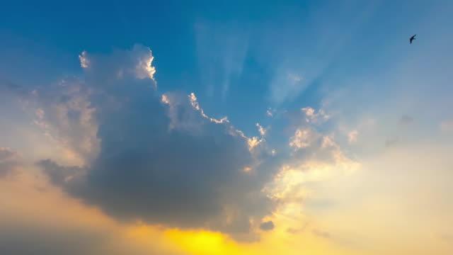 青空の雲を通して輝くタイムラプスサンセット - 希望点の映像素材/bロール