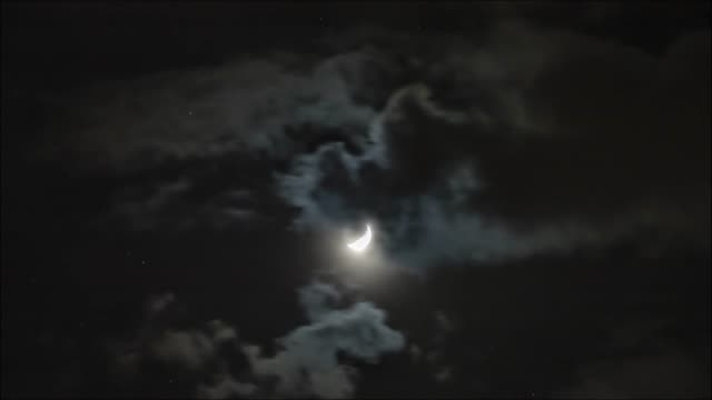 Time lapse: the moon lighting through clouds in dark night sky. 4K