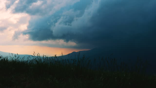 Time lapse. Thick thunderstorm clouds float over mountainous territory.