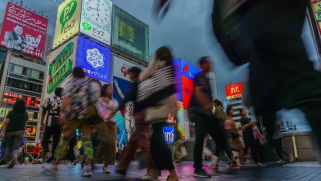 4kタイムラプスチルトダウン、ペデサルダウン.道頓堀を歩く人たち、 大阪 、 日本 . - 斜めから見た図点の映像素材/bロール