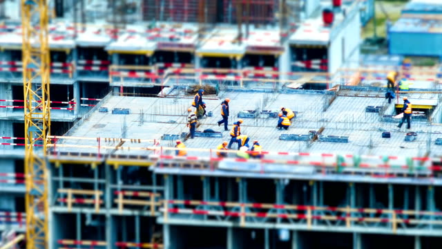 Time lapse tilt shift builders and cranes working on the construction site close up, zoom