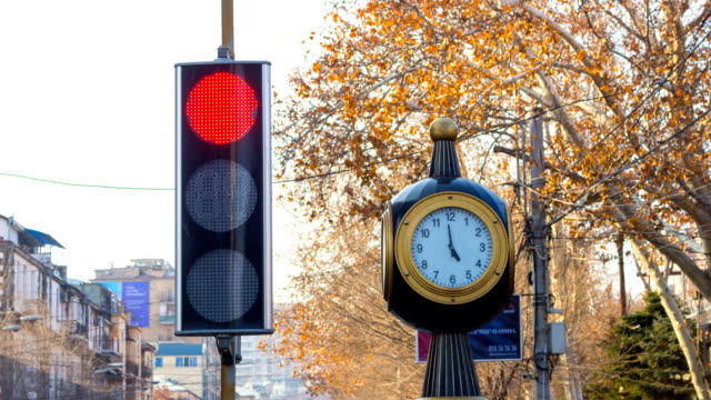 Time lapse: traffic lights with a clock on the city background with trees. video