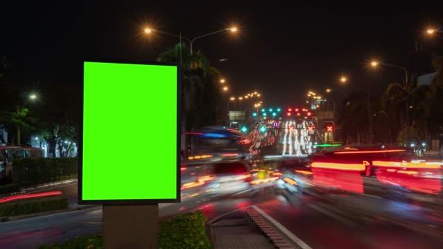 vídeos de stock, filmes e b-roll de time lapse, tráfego longa exposição na estrada com a billboard uso da tela verde para a publicidade de sinais de rua na cidade. - poster