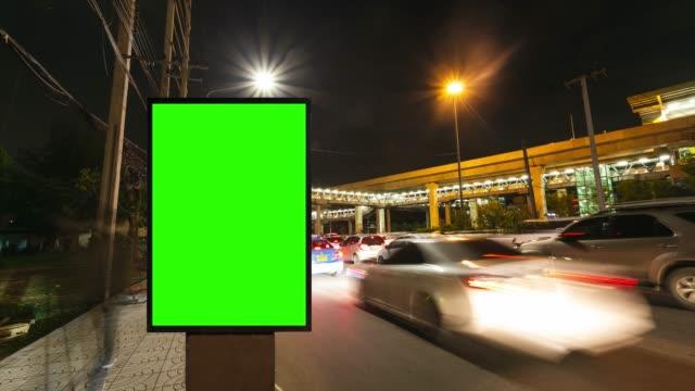 vídeos de stock, filmes e b-roll de lapso de tempo, longa exposição de tráfego na estrada com uso de tela verde para publicidade de placas de rua na cidade. - poster
