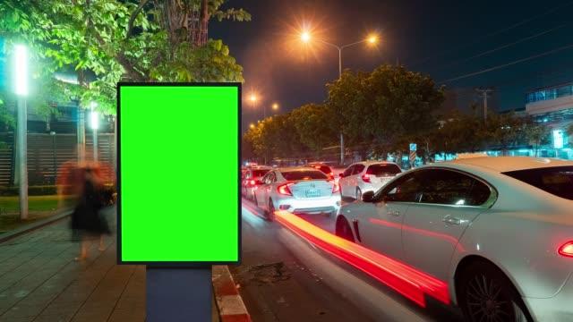 zeitraffer, verkehrsnacht lange belichtung auf der straße mit billboard green screen verwendung für werbung. - plakat stock-videos und b-roll-filmmaterial
