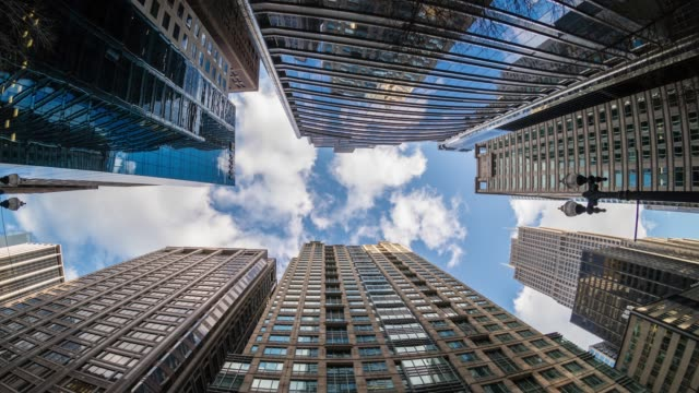 4k zeitraffer uprisen winkel von downtown chicago wolkenkratzer mit reflexion der wolken zwischen hohen gebäuden in fisheye winkel, illinois, usa, business and perspective konzept - turm bauwerk stock-videos und b-roll-filmmaterial