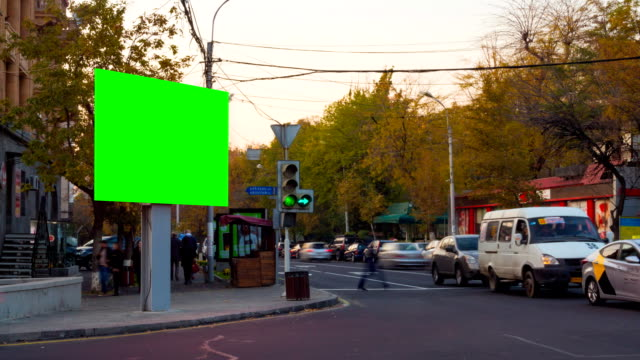 4K Time Lapse video. Big biilboard with green screen the against backgrounds of blurred cars and people in autumn city. The camera moves away