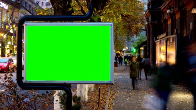 zeit lapse video. große plakatwand mit grüner leinwand vor dem hintergrund von fußurlosen menschen in herbststadt. - plakat stock-videos und b-roll-filmmaterial