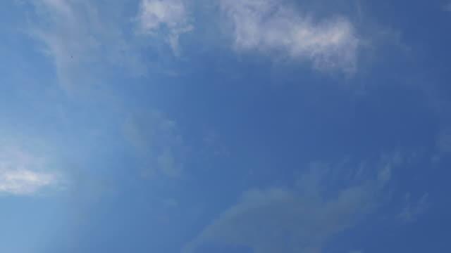 vídeos de stock, filmes e b-roll de captura de vídeo de lapso de tempo em nuvens moventes de 24fps durante um dia ensolarado no fundo do céu azul na cidade entre edifícios na velocidade rápida. - só céu