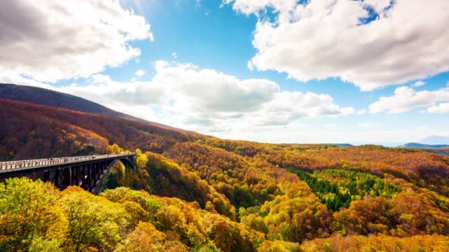 Time lapse video Jogakura Bridge in aomori city with Autumn Leaves background and movement cloud A wonderful view of Jyogakura-keiryu Stream a famous place in the Towada-hachimantai National Park.