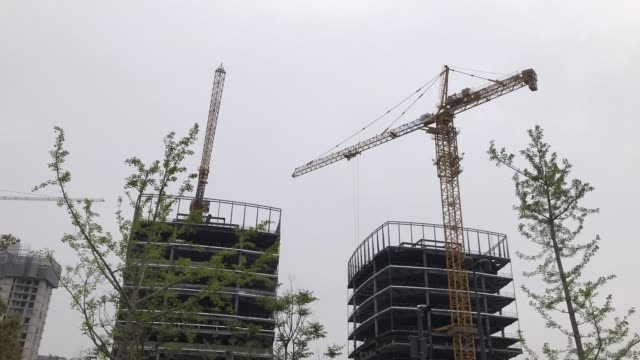 Time lapse video, the two crane machine in the construction site lifting heavy materials for the building
