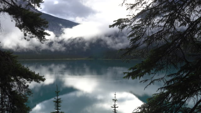 Time lapse view of clouds drifting above mountain lake video