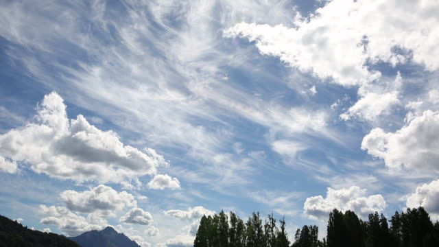 Time lapse view of clouds passing overhead meadow, mountains - vídeo