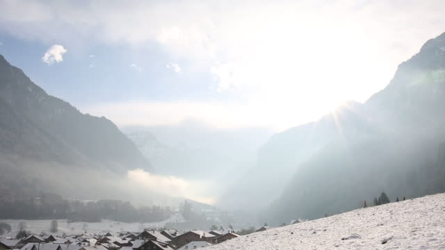 Time lapse view of clouds passing overhead mountains, village video