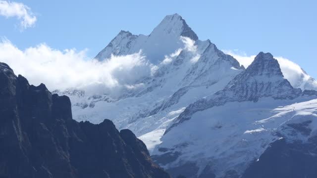 stockvideo's en b-roll-footage met time lapse uitzicht op wolken wervelende rond berg toppen - sneeuwkap