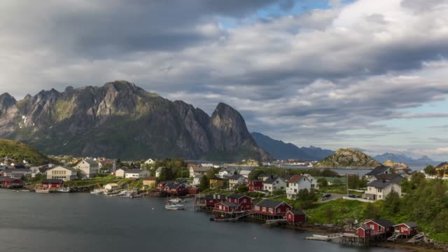 vídeos de stock e filmes b-roll de time lapse view of reine fishing village with mountain range in the background - reine